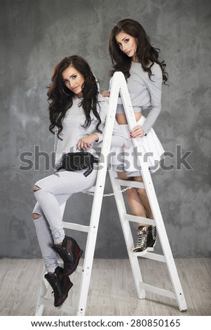 Two Pretty cheerful fashion  model on ladder in studio - stock photo