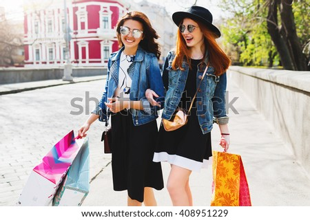Two pretty cheerful women shopping in city ,walking in the streets, talking, happy emotions.   Friends enjoying shopping day on their vacation in Europe.  - stock photo