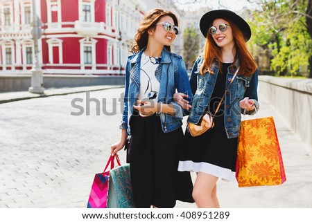 Two pretty cheerful women shopping in city ,walking in the streets, talking, happy emotions.   Friends enjoying shopping day on their vacation in Europe.