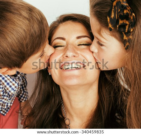two pretty children kissing their mother close up, happy family, brother and sister - stock photo