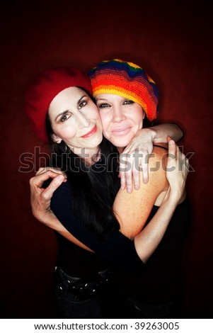 Two pretty female friends hugging and wearing knit hats