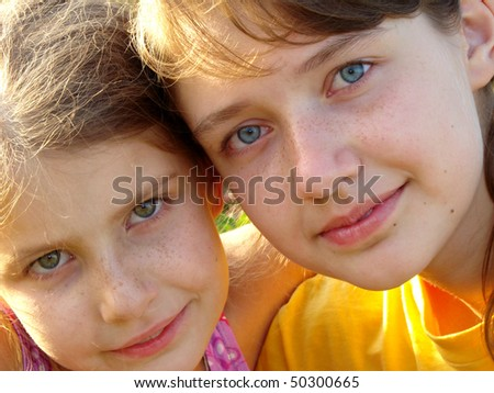 two pretty freckles sisters summer outdoor portrait - stock photo
