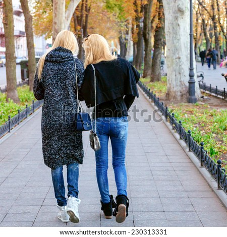 Two pretty friend walking together at city avenue. Fashion fall autumn portrait of stylish blondes wearing trendy cozy casual outfits. Speaking and having fun together.