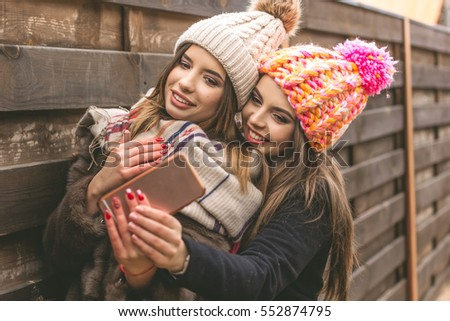 Two pretty girl are taking selfie with smartphone