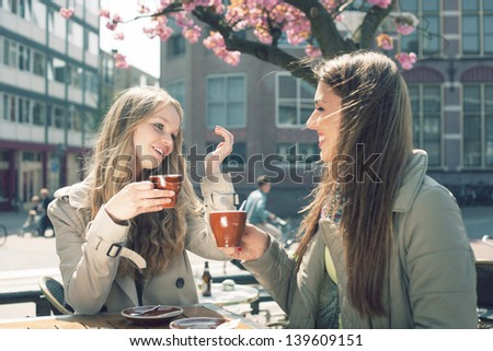Two pretty girl-friends talk and drink tea in cafe, outdoors - stock photo