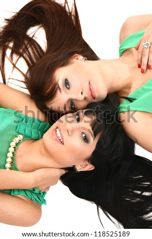 Two pretty girlfriend  lie on a white background - stock photo