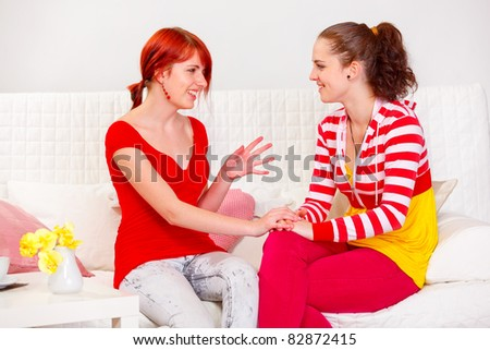 Two pretty girlfriends sitting on sofa at home and talking - stock photo