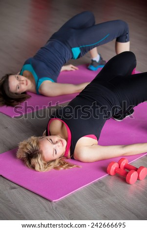 Two pretty girls do fitness exercises for hips and buttocks in lying position on mats in sports hall - stock photo