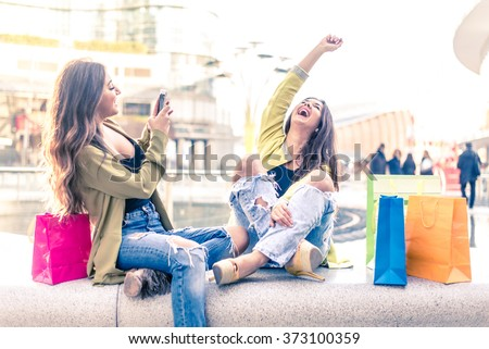 Two pretty girls having fun while shopping outdoors - Best female friends spending time together - stock photo