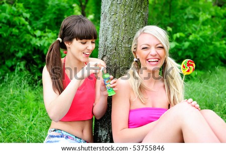 two pretty girls having fun with candys - stock photo