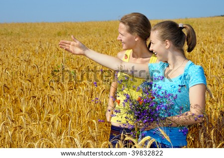 Two pretty girls in an excitement of sight on golden field