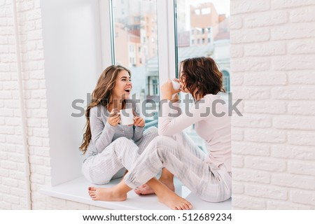 Two pretty girls pajamas sitting on 512689234 shutterstock two pretty girls in pajamas sitting on window in light room they drinking tee and voltagebd Choice Image