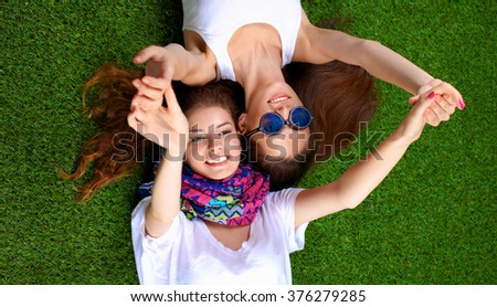 Two pretty girls lying on the fresh green grass  - stock photo