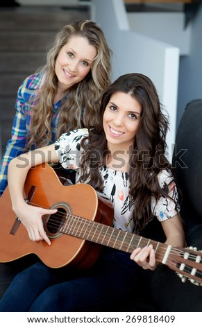 Two pretty girls playing guitar at home - stock photo