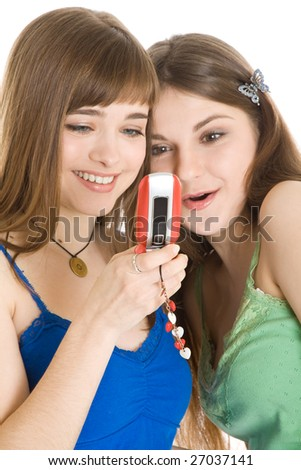 Two pretty girls reading SMS on mobile phone isolated on white background - stock photo
