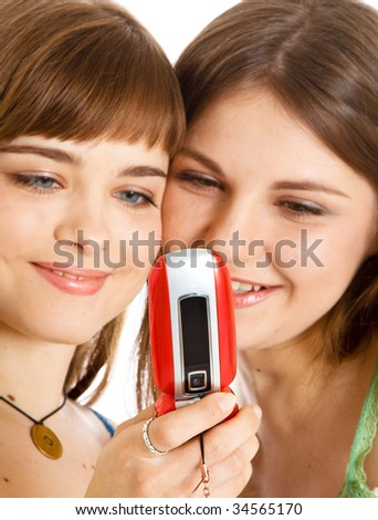 Two pretty girls reading SMS on mobile phone. Isolated on white background - stock photo