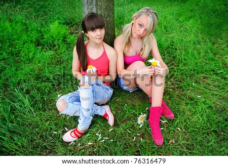 two pretty girls relaxing outdoor - stock photo