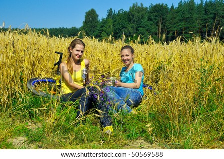 Two pretty girls rest from riding bike in golden field