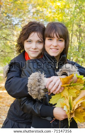 Two pretty girls  standing outdoors in autumn - stock photo