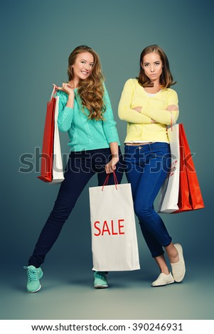Two pretty girls standing with shopping bags and smiling happily. Beauty, fashion. Sale, shopping concept.