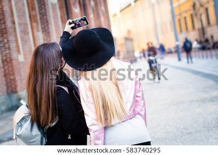 Two pretty girls taking selfie, rear view, streets of Milan, Italy.