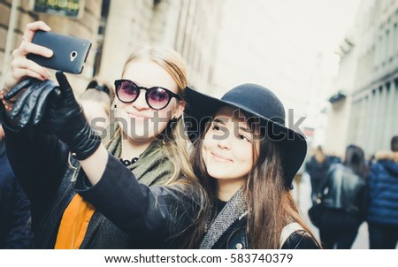 Two pretty girls taking selfie, streets of Milan, Italy.