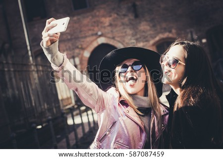 Two pretty girls walking and taking selfie. Streets of Milan, Italy.