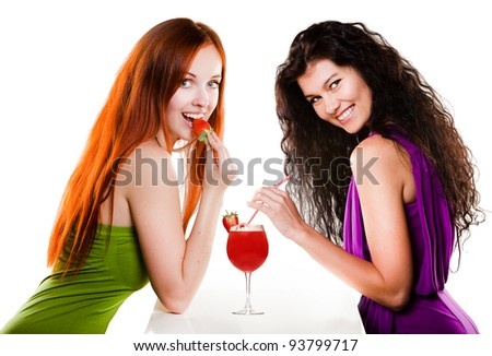 Two pretty girls with a strawberry cocktail - stock photo
