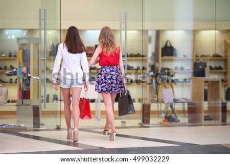 Two pretty girls with bags walk in big modern shop, back view