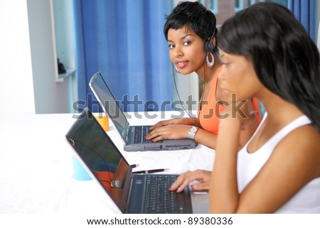 Two pretty girls working on laptops, horizontal image with selective focus - stock photo