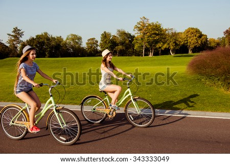 two pretty happy  girls  riding a bicycle on park - stock photo