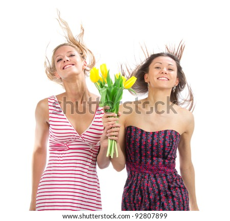 Two pretty happy girls with bouquet of tulips flowers walking smiling isolated on a white background - stock photo