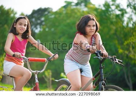 Two pretty hispanic children riding on their bikes - stock photo