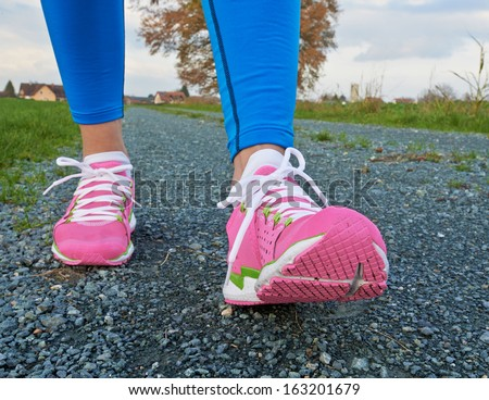 Two pretty legs in pink shoes walking to camera - stock photo