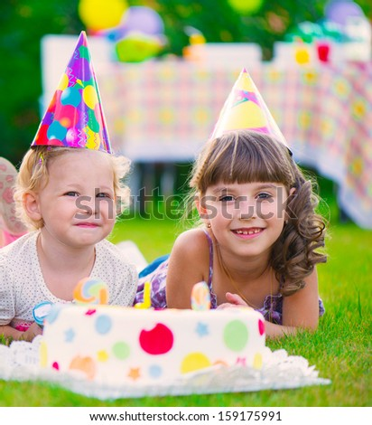 Two pretty little girls celebrating birthday on green grass - stock photo