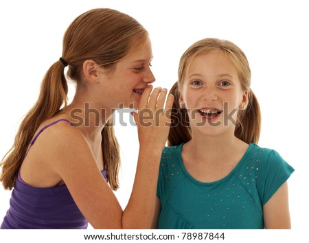 two pretty little girls telling secrets and giggling - stock photo