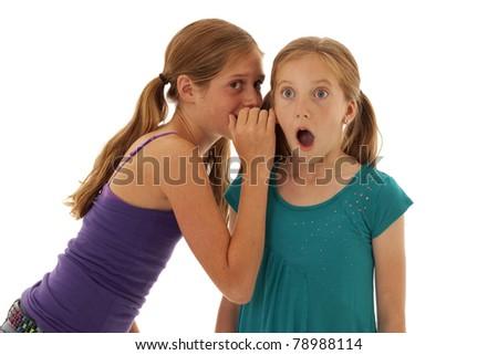 two pretty little girls telling shocking secrets - stock photo