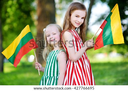 Two pretty little sisters holding tricolor Lithuanian flags on Lithuanian Statehood Day - stock photo