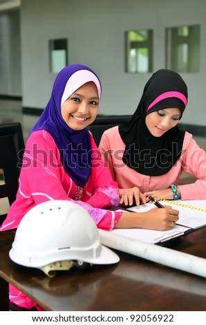 Two pretty muslim women give a smile while busy with work - stock photo