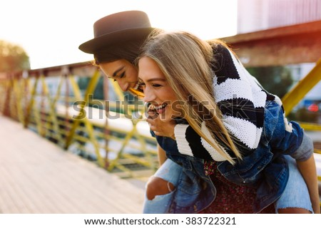 Two pretty sisters hipster girls hugs and having fun together, wearing trendy clothes, positive emotions, bright colors - stock photo