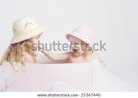 Two pretty sisters of 2 and 4 years old in summer bonnets sitting in big pink box - stock photo