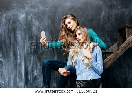 Two pretty sisters women with Healthy Long Hair ringlets wearing knit sweaters taking selfie by smartphone