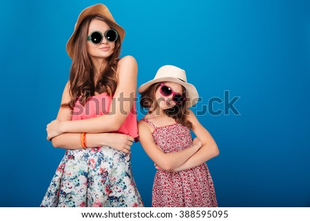 Two pretty smiling sisters standing and posing with hands folded over blue background - stock photo