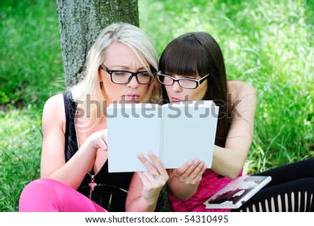 two pretty student girls reading book with no title - stock photo