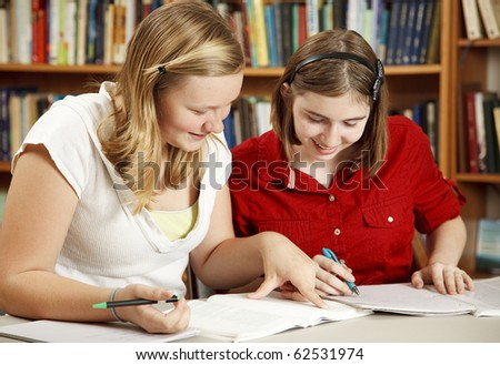 Two pretty teen girls doing their homework in the school library. - stock photo