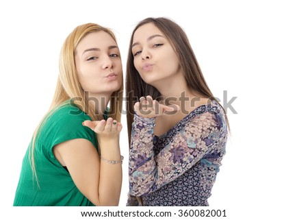 Two pretty teenage girls -blonde and brunette- sending kisses over white background - stock photo