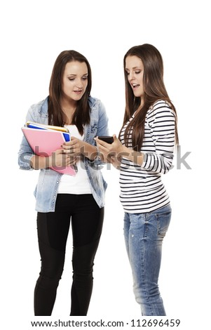 two pretty teenage students looking at a smartphone on white background - stock photo