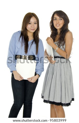 Two pretty university student girl poses over white background.