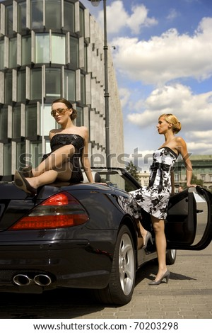 two pretty woman in black exclisive car - stock photo
