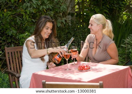 Two pretty women enjoying a glass of wine on a sunny afternoon - stock photo